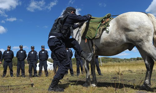 A policeman mounts his horse. Photo: CFP