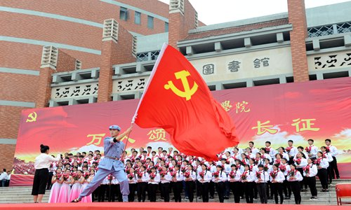 Faculty members and students from Huainan Normal University in East China's Anhui Province sing a revolutionary song to commemorate 80th anniversary of the Long March (1934-36) of the Red Army on Wednesday. Photo: CFP