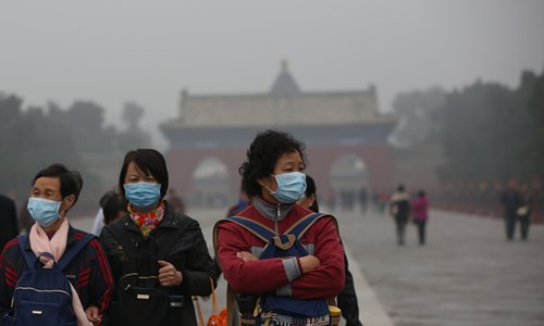 Tourists wearing face masks visit the Temple of Heaven, also known as Tiantan, in heavy smog in Beijing on Wednesday. Photo: IC