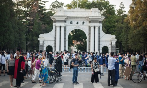 Graduating students take pictures in front of the landmark gate of Tsinghua University on July 2. Photo: IC