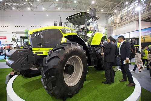 Visitors view a tractor during the 2016 China International Agricultural Machinery Exhibition in Wuhan, capital of central China's Hubei Province, Oct. 26, 2016. About 1,900 companies took part in the exhibition held at Wuhan International Convention and Exhibition Center. (Xinhua/Xiong Qi)