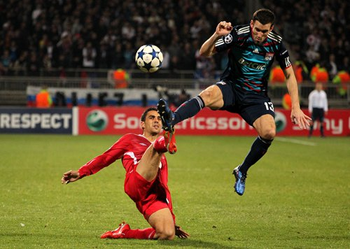 Hapoel Tel Aviv's Eran Zahavi (left) and Lyon's Anthony Réveillère battle for the ball.