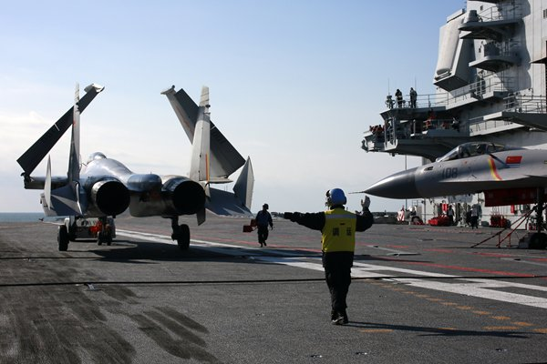 An officer gives directions to a fighter jet on the flight deck of the Liaoning. Photo: Zhang Kai