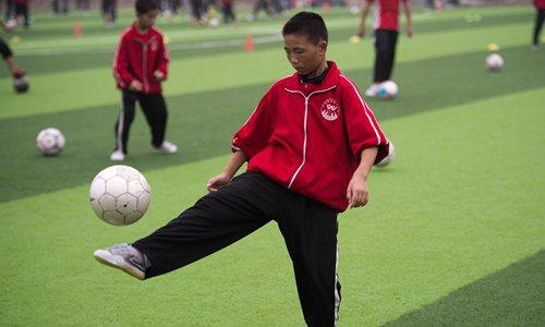 A student kicks a soccer ball. Photo: CFP