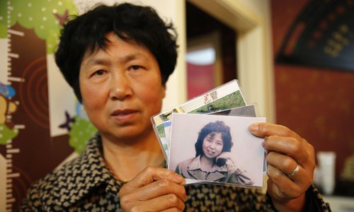 Yang Kailan displays pictures of her abandoned sister, which she had kept with her since she first saw them on WeChat. Photo: CFP