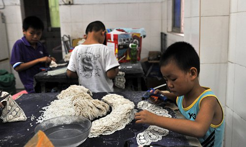 Children assemble necklaces at a pearl factory in Dongguan, Guangdong Province. Photo: CFP