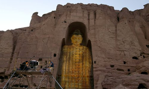 Workmen project the image of a Buddha statue that had been destroyed by the Taliban in 2001 on June 7, 2015 in Bamiyan, Afganistan. Photo: AFP