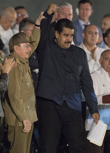Cuban President Raul Castro (left) raises the hand of Venezuelan President Nicolas Maduro during a mass rally on Tuesday on Revolution Square in Havana in honor of the late Cuban leader Fidel Castro. Photo: AFP