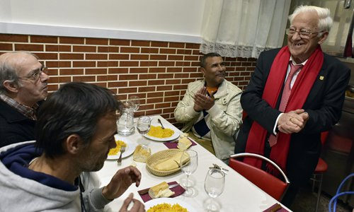 Angel Garcia (right) speaks with homeless people at the Robin Hood restaurant in Madrid on December 1. Photos: AFP