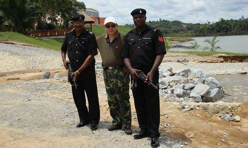 Hu Jieguo poses with two police guards in Lagos, Nigeria. Photo: Courtesy of Hu Jieguo