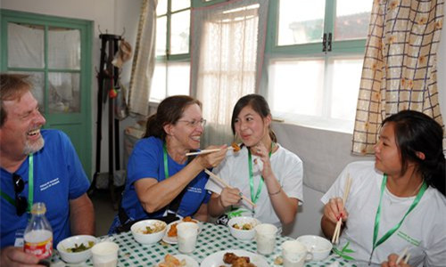 Children adopted from China by American parents eat at a camp in Beijing to help them learn more about their origins. Photo: CFP