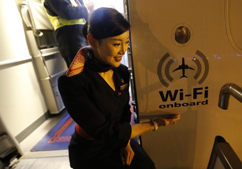 An air stewardess stands by a Wi-Fi logo on a Chinese Eastern Airlines flight in January in Qingdao, East China's Shandong Province. Photo: CFP