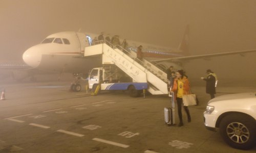Passengers disembark a plane which was delayed due to heavy smog at the Qingdao Liuting International Airport in Qingdao, East China's Shandong Province on Monday. Several flights had been delayed or cancelled in Qingdao due to the smoggy weather. Photo: CFP