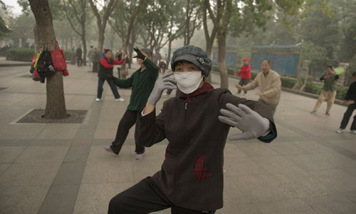 People dance in the park with masks on during a smoggy day. Photo: Li Hao/GT