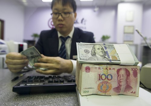 A bank employee counts US dollars on Wednesday in Taiyuan, capital of North China's Shanxi Province. Photo: CFP