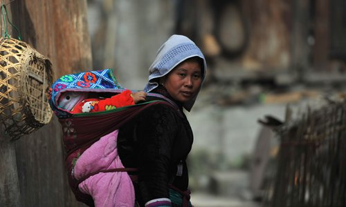 A villager carries a baby on her back. Photo: IC