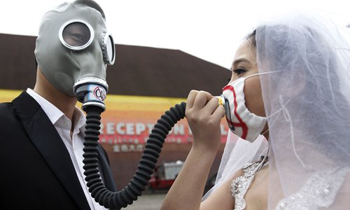 Artists dressed up as a couple pretend to get married while wearing masks in Chengdu, Sichuan Province in 2014 to show their concerns about air pollution.Photo:IC