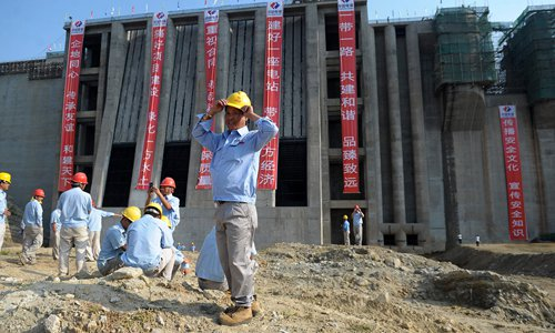 Chinese construction workers stand in front of the Moraghakanda reservoir in Sri Lanka on Wednesday. Sri Lanka President Maithripala Sirisena attended the inauguration of the filling of the project on the same day, AFP reported. The $220 million reservoir will reportedly help more than 10,000 farmers in the northern and eastern parts of the island get more water for irrigation. Photo: CFP