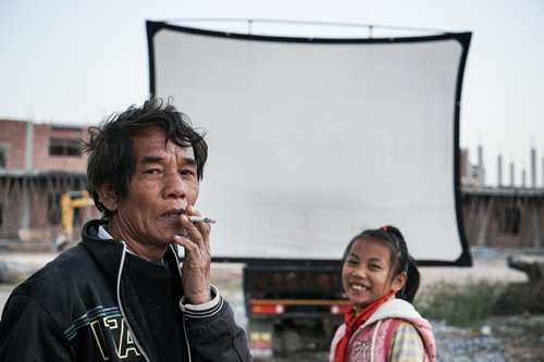 A farmer and a girl from Bancheng village wait in front of the screen that Luo has hung up to watch movie. Photo: CFP