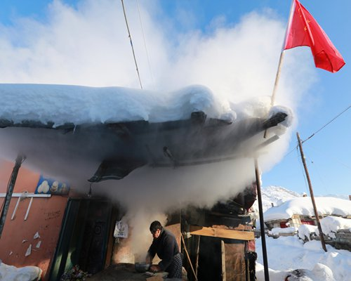 A man cooks nang (a traditional Uyghur flatbread) in freezing temperatures in Koktokay township, Northwest China's Xinjiang Uyghur Autonomous Region. January is the coldest month in Koktokay, with the average temperature of -37 C. Photo: CFP