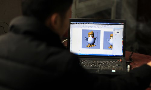 A designer looks at a 3D model of the rooster on a computer. Photo: Yang Hui/GT