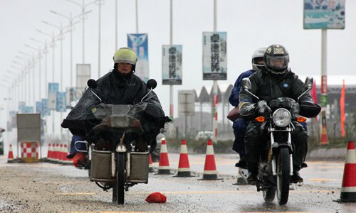 Riders hit the road wearing everything they have, padded coats, raincoats, helmets and gloves. Photo: IC