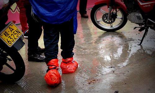 Riders wrap their feet in layers of plastic bags to keep them warm and dry. Photo: IC