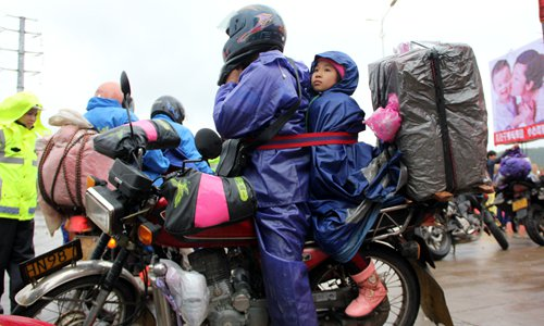 Guo is strapped to her father's back to keep her from falling off the bike. Photo: IC