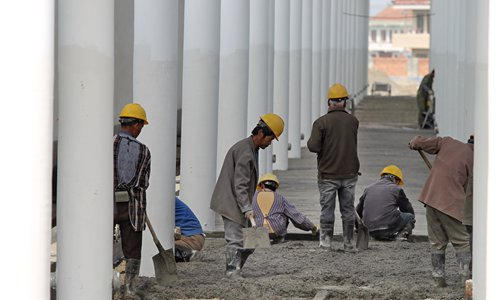 Migrant workers build a train station. Photo:CFP