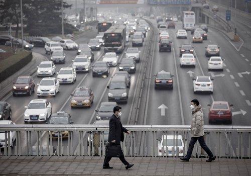 Pedestrians wearing face masks walk across a footbridge over a highway in Beijing on January 6. Photo: CFP