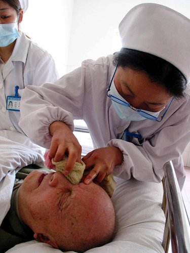 A nurse in an asylum in Nanjing, East China's Jiangsu Province cleans the face of a patient  who's confined to the bed. Photo: CFP