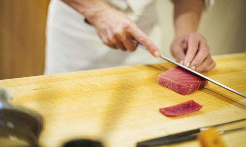 A chef slices fish for making sushi. Photo: IC