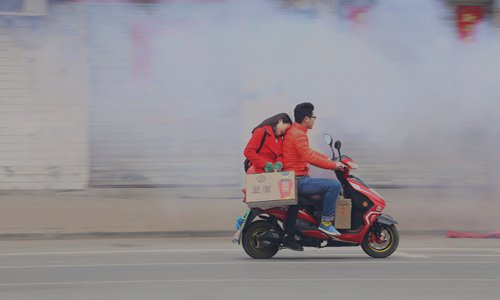 A couple on a motorcycle passes heavy smoke emitted from fireworks on Spring Festival in Hefei, Anhui Province. Photo: IC