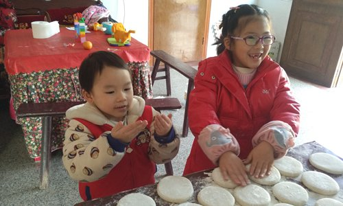 Children help their parents make traditional rice cakes before the eve of Spring Festival. Photo: Huang Jingjing/GT