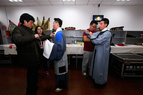 Yu Hui (middle) puts on his costume with the help of co-workers.