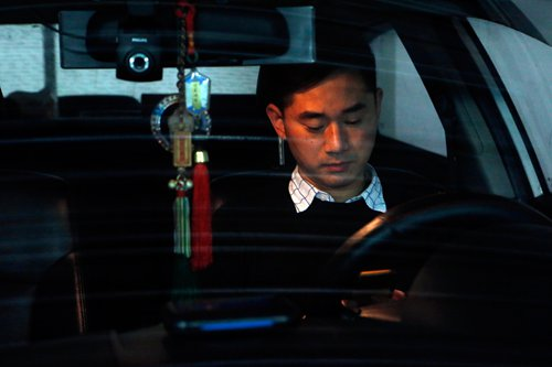 Yu Hui enjoys a relaxing moment in his car after class.