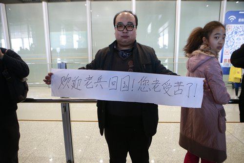 A man raises a banner to welcome Wang Qi back to China at Beijing Capital International Airport before Wang transferred to a flight to Xi'an on Saturday. Photo: Li Hao/GT