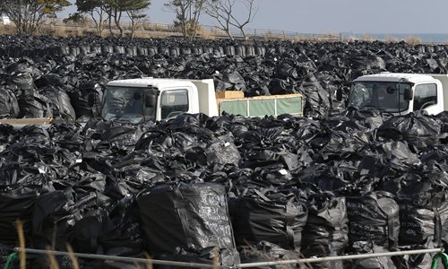 Trash bags filled with collected radioactive soils, plants and other trash are packed at a temporary waste storage site in Tomioka, Fukushima prefecture, Japan on February 24, 2016. Photo: IC