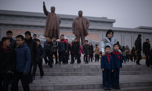 A woman and two children pose for a photo as they visit the statues of late North Korean leaders Kim Il-sung and Kim Jong-il to pay their respects on the occasion of the 75th anniversary of the birth of Kim Jong-il, at Mansudae Hill in Pyongyang on Thursday. Photo: AFP
