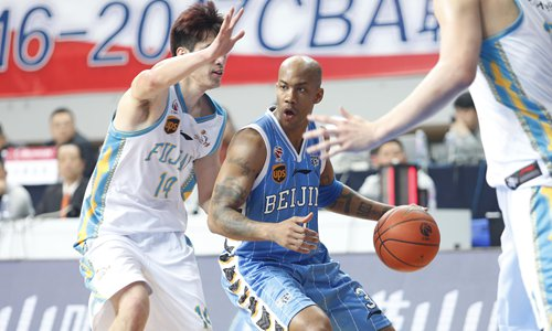 Stephon Marbury (middle) of the Beijing Ducks dribbles the ball against the Fujian Sturgeons during Friday's CBA match in Jinjiang, East China's Fujian Province. Beijing won 110-98 to put themselves back to the eighth place in the league, the final berth for CBA playoffs. They will host seventh-placed Sichuan Whales on Sunday in the regular-season final round. But a defeat will jeopardize the Ducks' chance for the playoffs. Photo: CFP