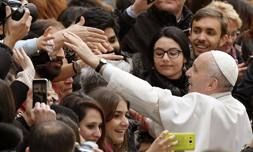 Pope Francis greets students as he arrives at the Roma Tre University for a meeting with students and teachers in Rome on Friday. There, he was reunited with Nour Essa, one of the Syrian refugees whom Francis brought back with him after visiting Lesbos, Greece, last year. Francis said at the university that the phenomenon of migration doesn't pose a danger to Europe's culture but rather a challenge for societies to grow. He also said that