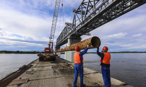 Workers transport tubes at the Tongjiang-Nizhneleninskoye Railway Bridge crossing over the Heilongjiang River (the Amur River) at Tongjiang, Northeast China's Heilongjiang Province in June. Photo: IC