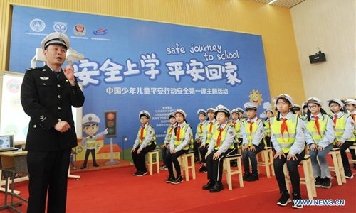 Pupils learn traffic knowledge from a police at Dongzhongshi Experimental Primary School in Suzhou, east China's Jiangsu Province, March 26, 2018, China's national safety education day for middle and primary school students. (Xinhua/Hang Xingwei)