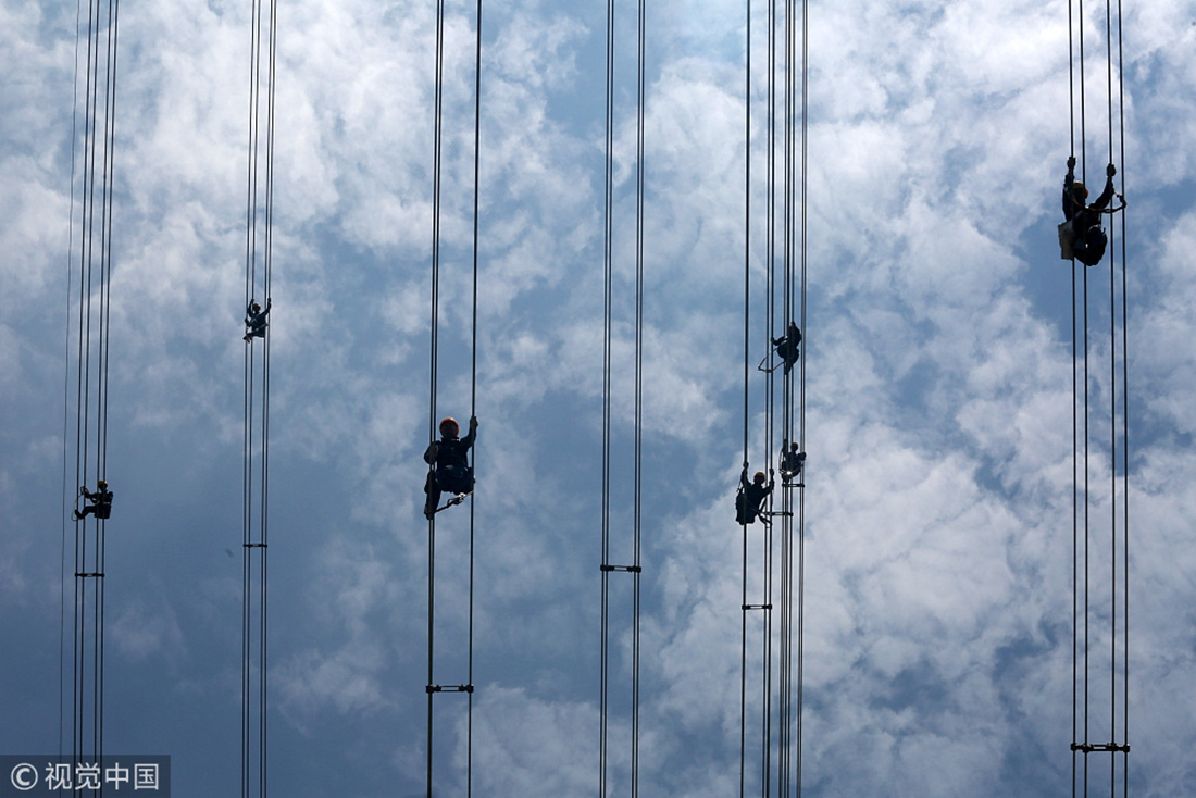 Electricians from China Southern Power Grid in Dongguan, Guangdong Province, check the high voltage cables hanging about 50 meters in the air on May 29, 2018. Photo: VCG