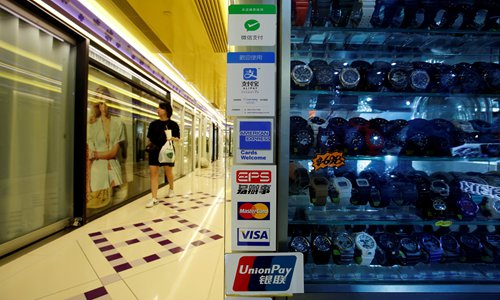 Inset: Logos of digital payment firms are displayed outside a store at a shopping mall in Hong Kong in July. Photo: VCG