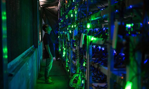 A worker checks on Bitcoin mining equipment at a facility in the Garze Tibetan Autonomous Prefecture, Southwest China's Sichuan Province. File photo: VCG