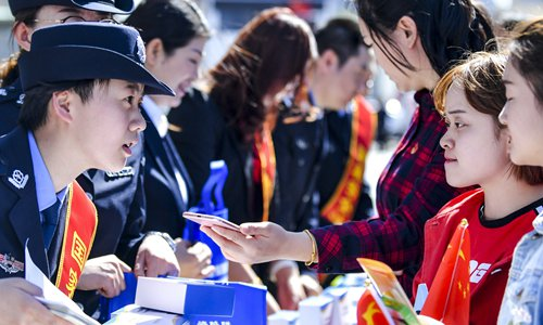 Police officer Zhu Wenzhen (left) from the anti-telecom network fraud center in Urumqi, Northwest China's Xinjiang Uyghur Autonomous Region, explains fraud detection skills to local residents on Monday, the 4th National Security Education Day. Photo: Xinhua