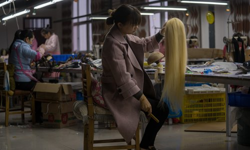 A worker combs a half-done wig at a wig factory in Xuchang, Central China's Henan Province. Photo: VCG