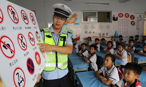 A police officer teaches pupils to recognize traffic signs at the No.1 Primary School of Boxing County in Binzhou City, east China's Shandong Province, June 27, 2019. Safety education activities are held across China to help raise students' awareness about safety for a safe summer vacation. (Xinhua/Chen Bin)