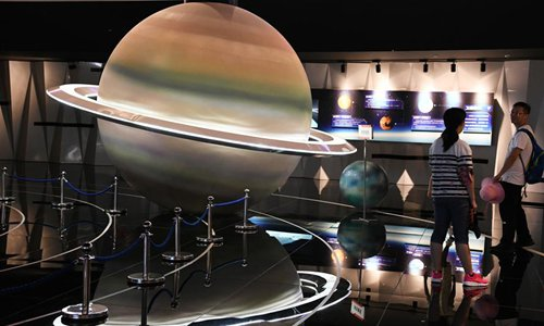 Visitors watch the solar system models at the astronomical museum in Pingtang during summer vacation in southwest China's Guizhou Province, July 24, 2019. (Xinhua/Yang Wenbin)